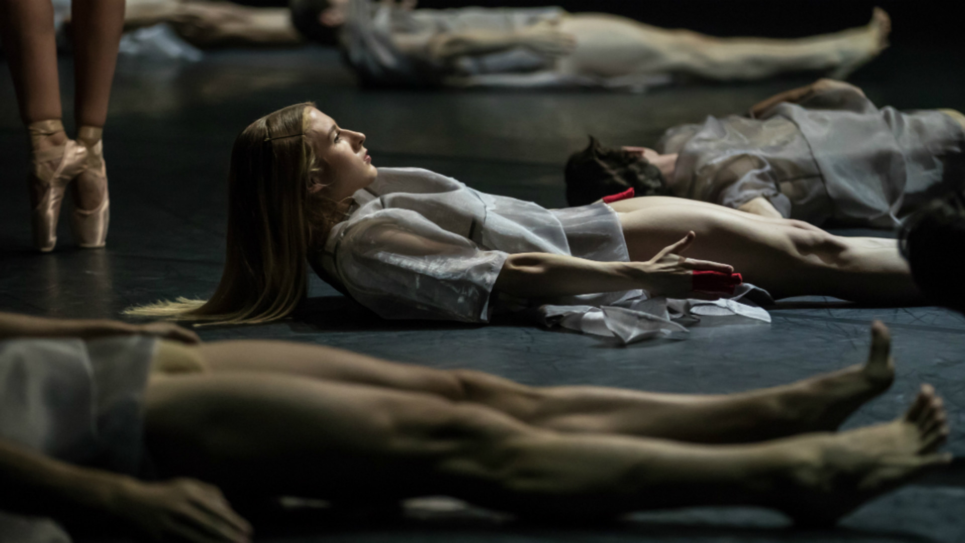 Dancers dressed in white lying on the floor with a dancers feet in pointe shoes to the side of the frame.