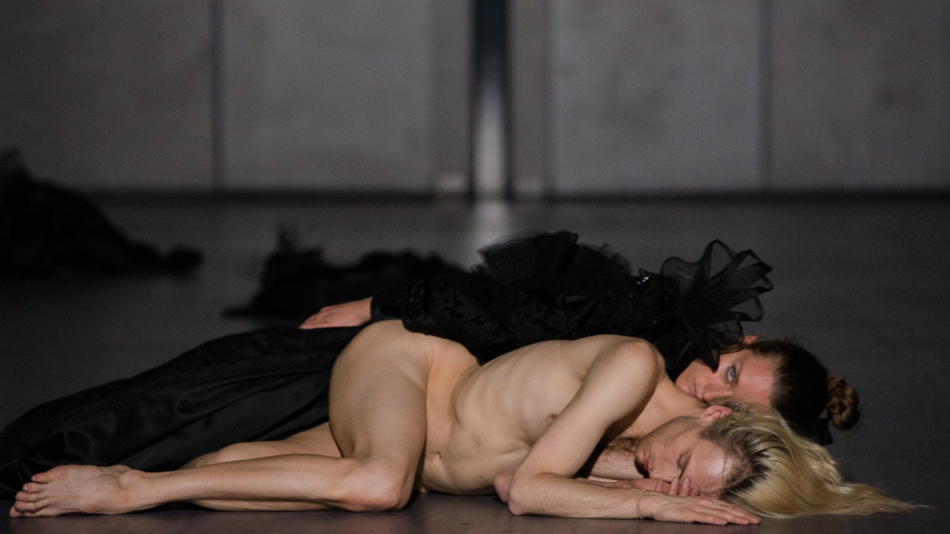 A dancer lies naked with another clothed dancer behind him.