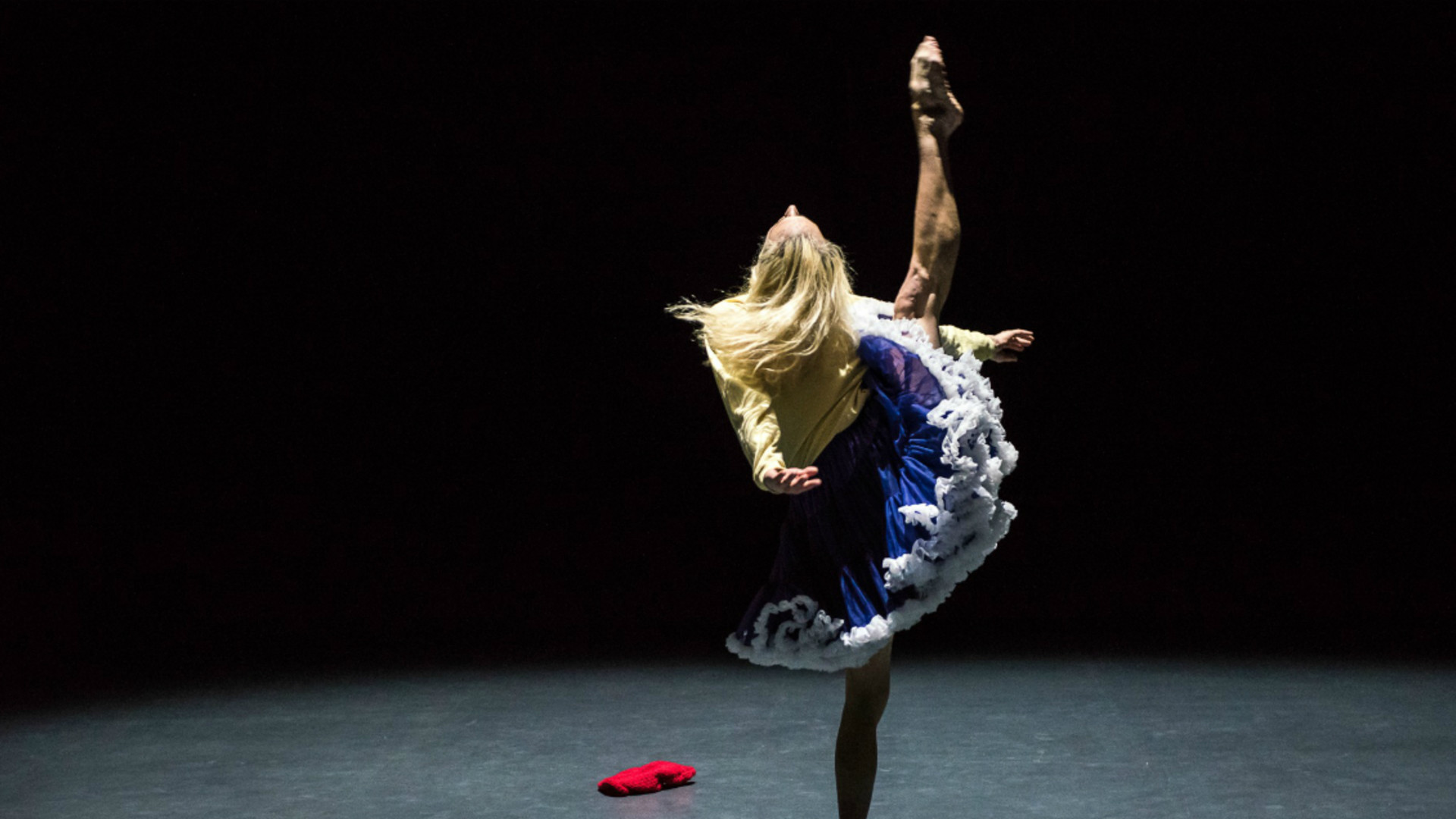 A dancer stands on one leg, with the other leg pointed and stretching upwards.