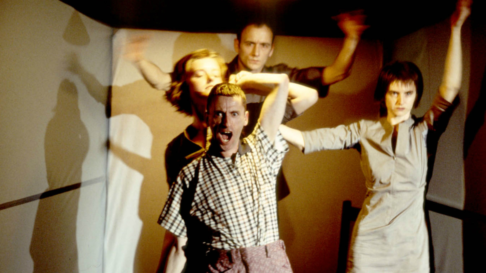 Four dancers in a small light room dressed in everyday clothes. Three wave their arms while one at the front appears to shout directly at us