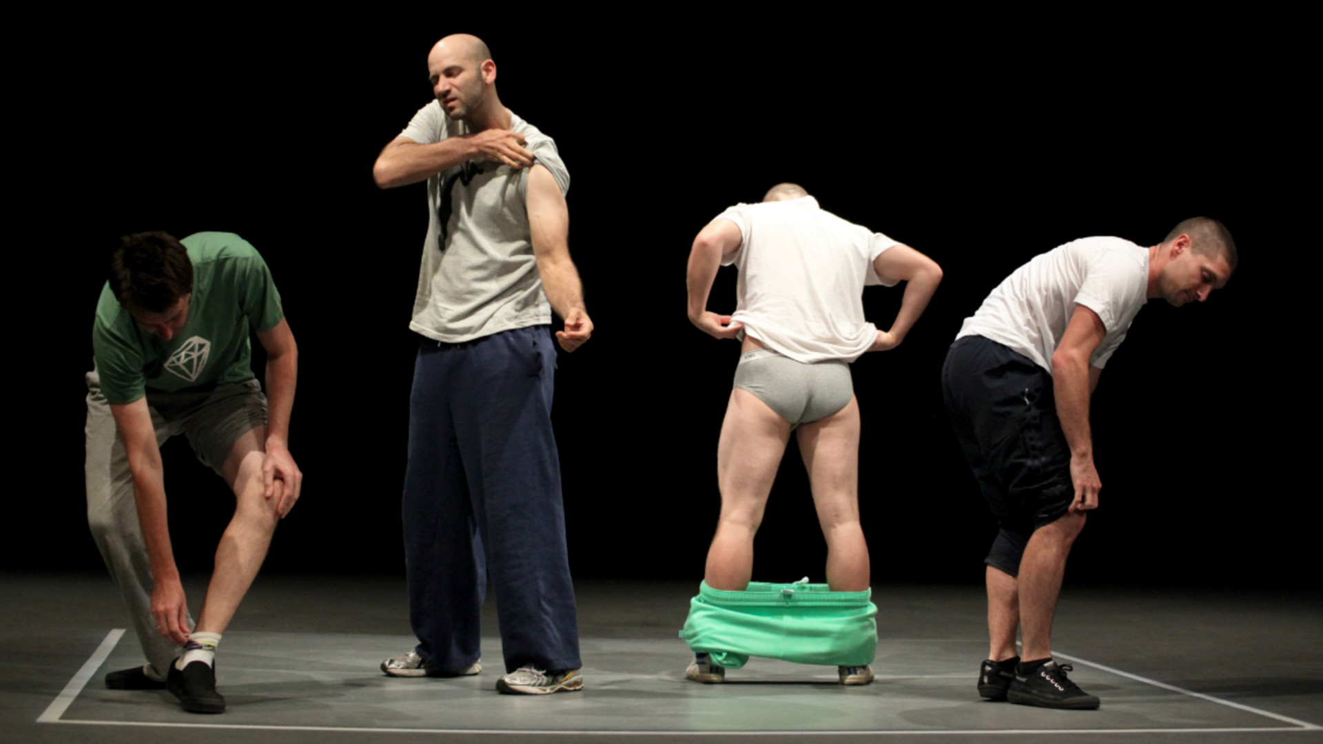 Dancers stand in a line. The first one is bent over pulling on his sock, the second stands upright lifting his tshirt sleeve, the third stands facing away with his pants around his ankles and the forth is bent over at the hip, facing sideways.