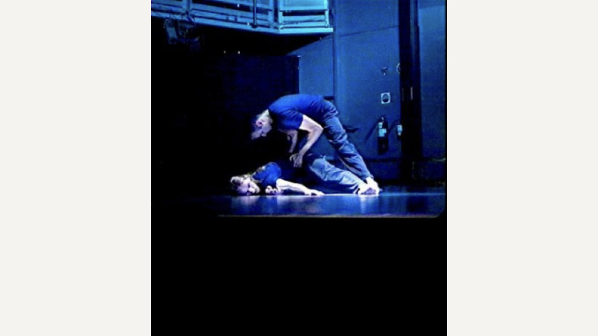 A dancer lunges over another who lies on their front in a blue room with theatre rigging just in view at the top